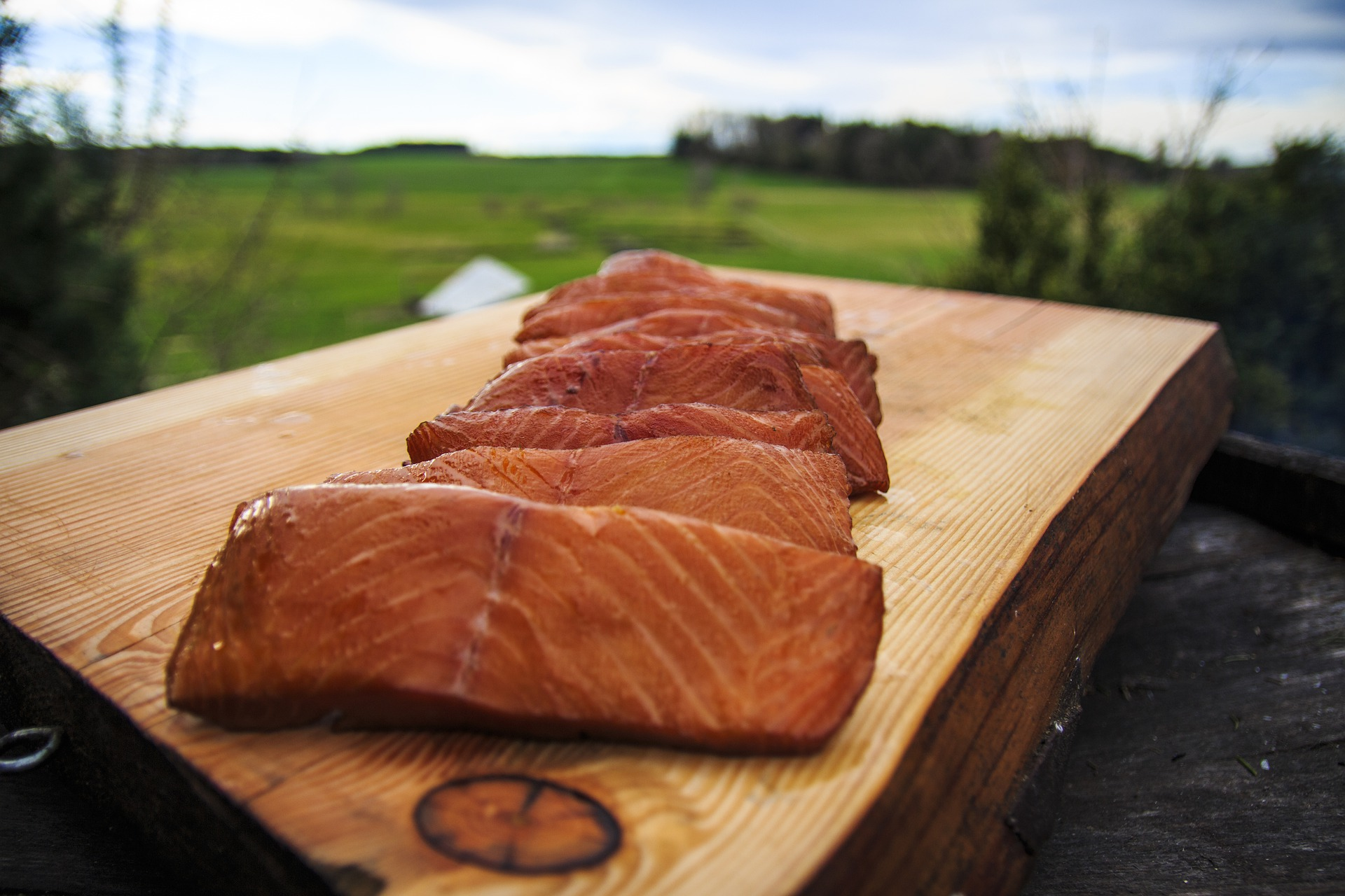 Photo of a bunch of smoked salmon on a wood plank