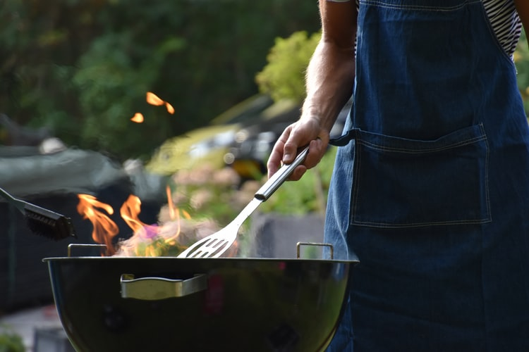 Man holding a spatula near a barbecue griller